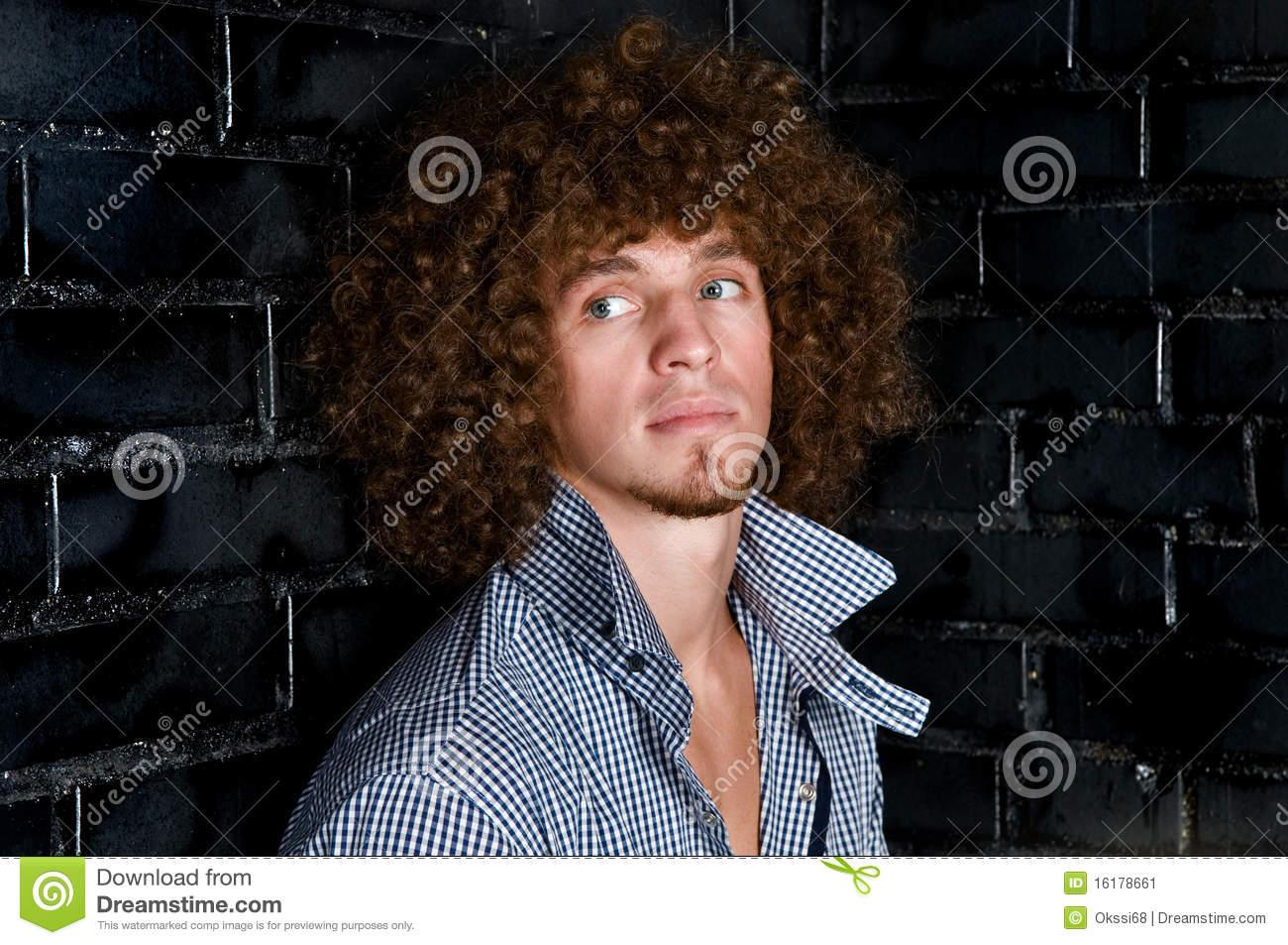 Portrait Young Man Curly Hair Against Black Wall